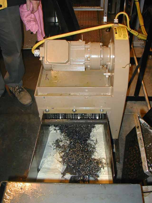 Rotary shredder with solids discharge, over a flume conveyor